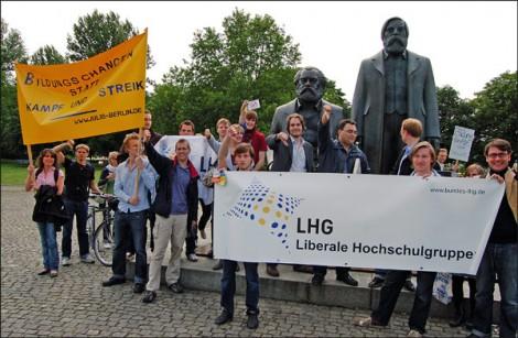 Die Bildungsstreikgegner posieren vor Karl Marx und Friedrich Engels.